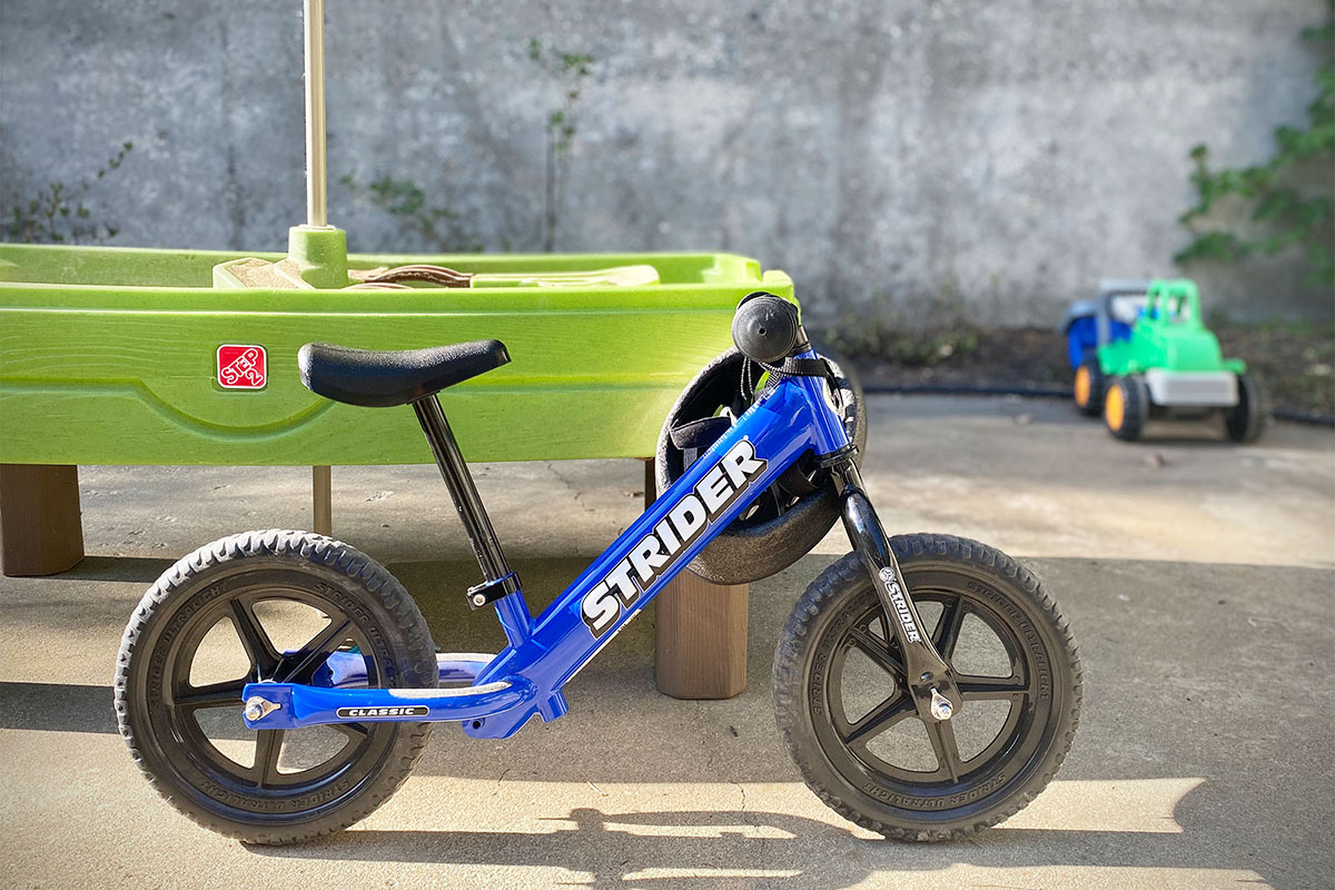 Strider Kids' Balance Bike (leaning against table)