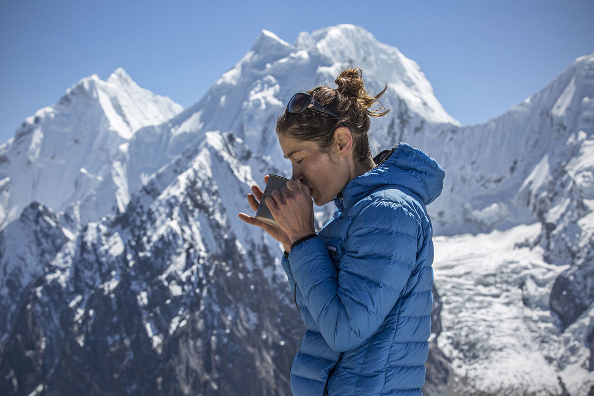 Wearing Feathered Friends Eos down jacket while drinking tea with mountains in background