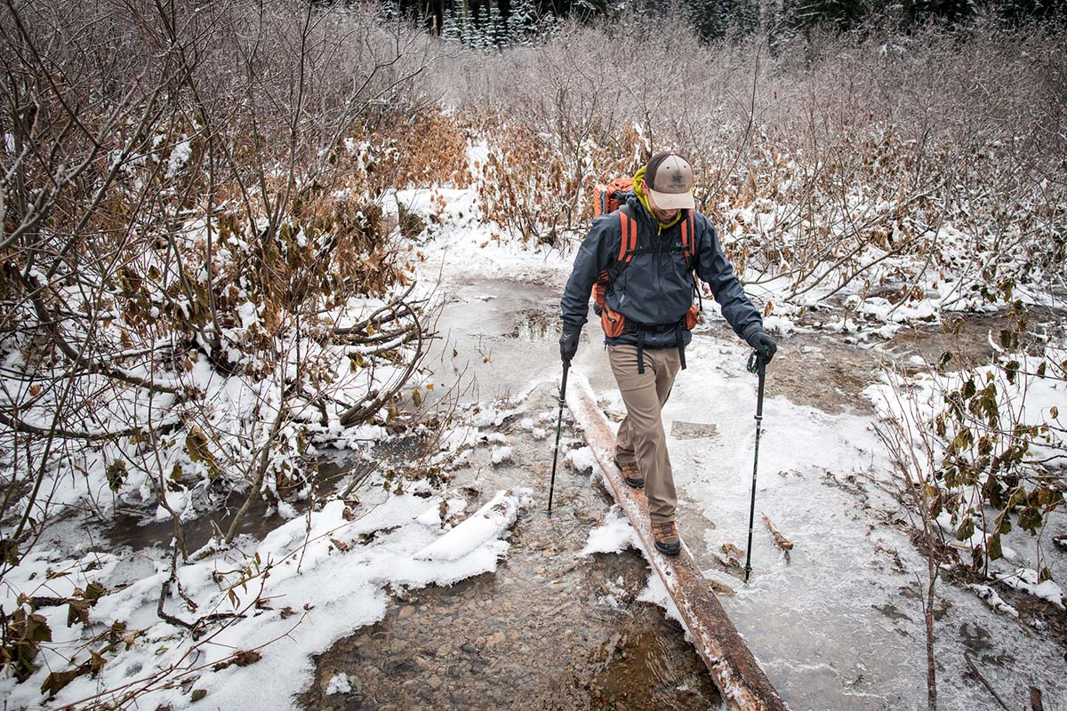Crossing log above frozen water (wearing Arc'teryx Beta AR hardshell jacket)