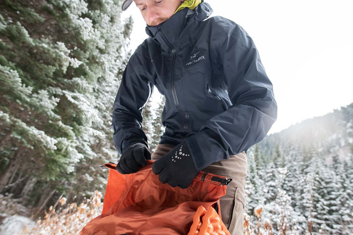 Packing backpack in snow (Arc'teryx Beta AR hardshell jacket tall collar)