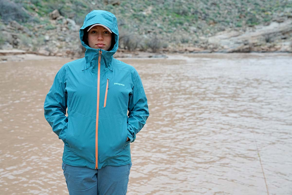 Woman standing in Patagonia Calcite rain jacket beside Colorado River