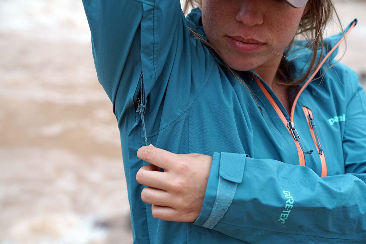 Woman unzipping pit zip of Patagonia Calcite Rain Jacket