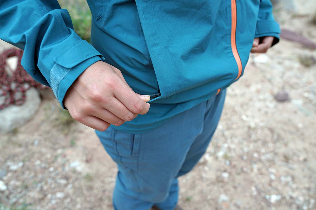 Zipping up handwarmer pocket in Patagnia Calcite rain jacket