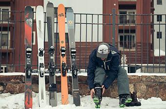 All-mountain skis (lined up against fence)