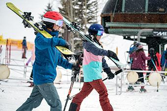 Ski Apparel (carrying skis beside chairlift at resort)